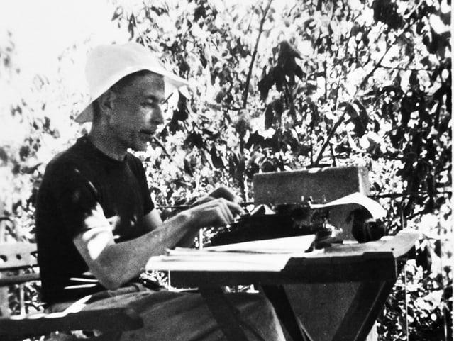 Friedrich Glauser, mit Hut und Zigarette im Mund draussen sitzend, auf einer Schreibmaschine schreibend.