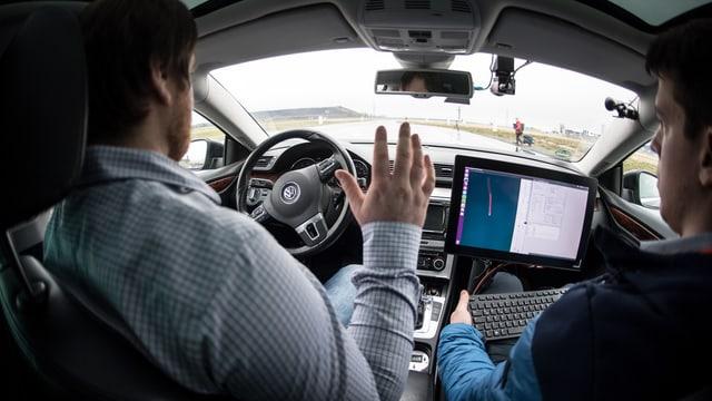 Zwei Männer in einem Auto, die Hände sind nicht am Lenkrad. Das Auto fährt autonom.