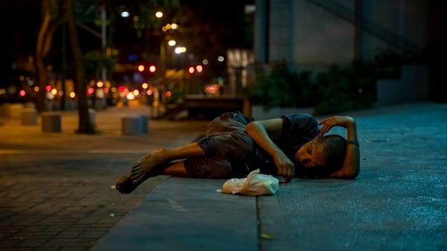 Ein verarmtes Kind schläft auf der Strasse.