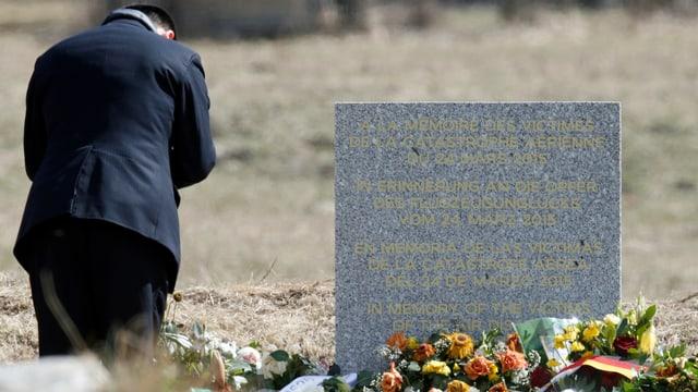 Mann neben Gedenktafel