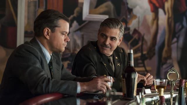 CloonMatt Damon im Anzug und Gerorge Clooney in Militäruniform sitzen an einer Bar.
