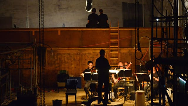 Bühne der Reithalle Aarau. Auf der Bühne sind Musiker und ein Dirigent.