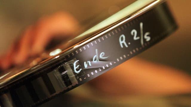 Auf Rolle gewickelter Filmstreifen, mit weissem Stift wurde «Ende R. 2/5» darauf geschrieben.