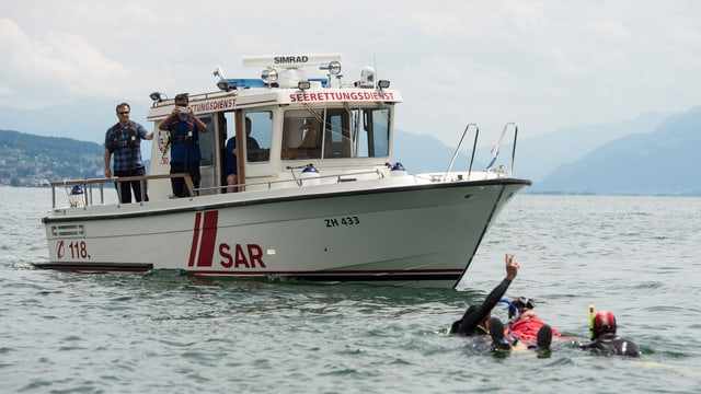 Ein Schiff steht auf dem Zürichsee. Daneben zwei Taucher, die eine verletzte Person bergen.