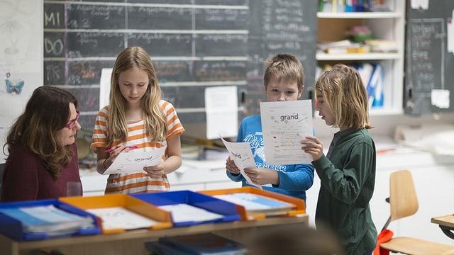 Lehrerin mit Schülern, diese halten Französisch-Arbeitsblatt in den Händen