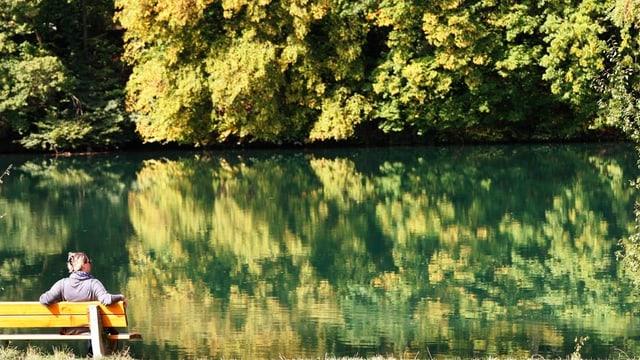 Frau auf Bank am Fluss