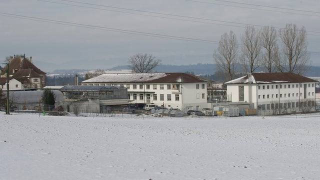 Blick auf zwei Gebäude der Anstalten Hindelbank, davor ein Feld mit Schnee.
