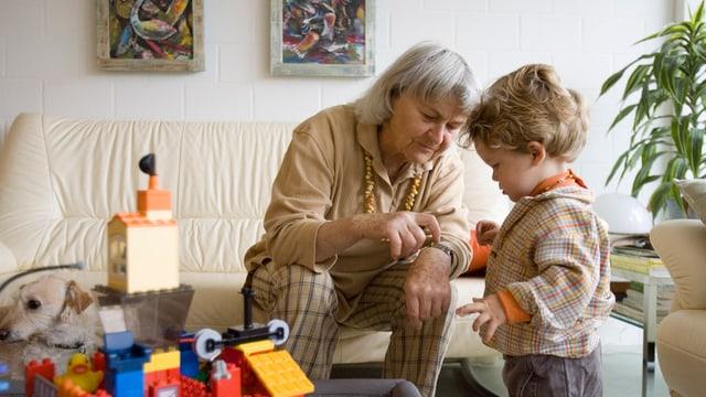 Eine ältere Frau spielt mit einem Kind.
