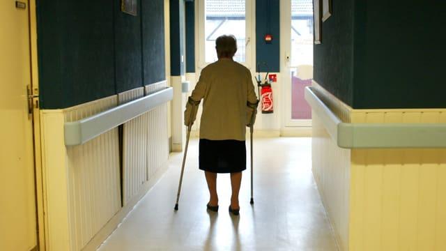 Eine Seniorin geht an Krücken den Gang entlang