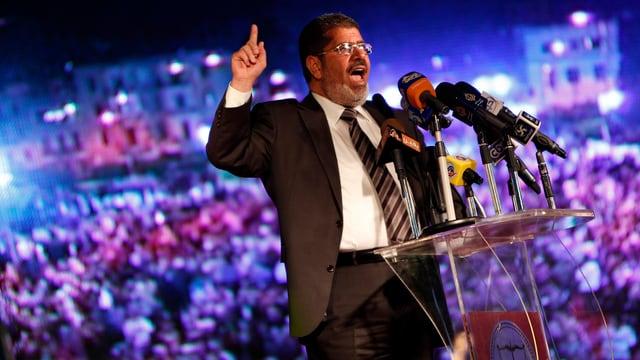 Mursi bei einer Rede, dahinter eine Volksmenge.