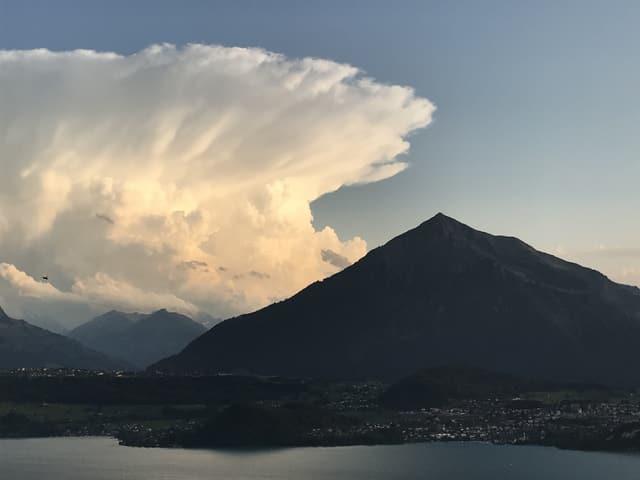 Im Vordergrund liegt der Niesen. Im Hintergrund steht eine mächtige Gewitterwolke mit einem Federbusch von Wolken an ihrem oberen Ende.