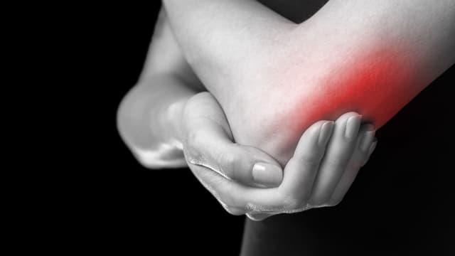 Frau hält sich schmerzenden Arm