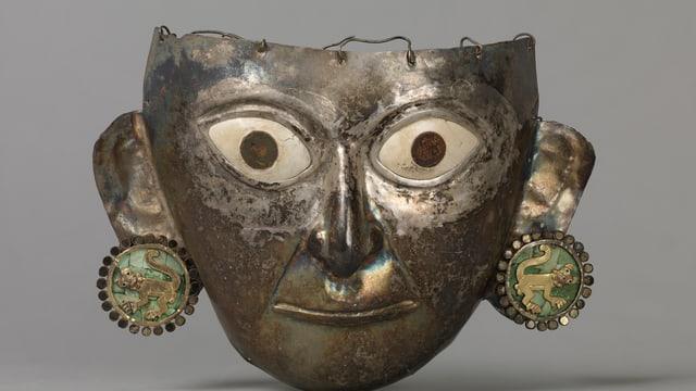 Eine peruanische Totenmaske aus Metall mit Ohrringen aus grüner Jade und Löwenfiguren.