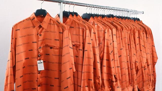 Orange Hemden auf einer Kleiderstange