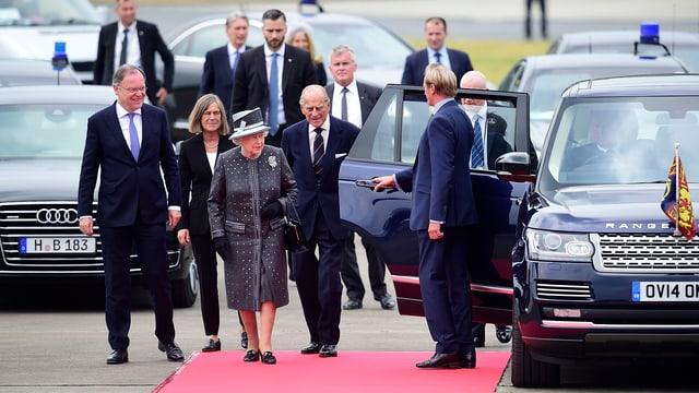 Ein Fahrer öffnet der Queen und Prinz Philip die Wagentür.