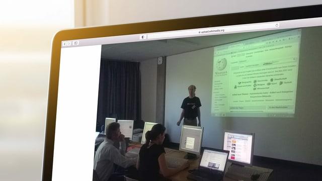 Ein Mann steht vor einer weissen Wand, auf der mit einem Projektor die Website von Wikipedia abgebildet ist.