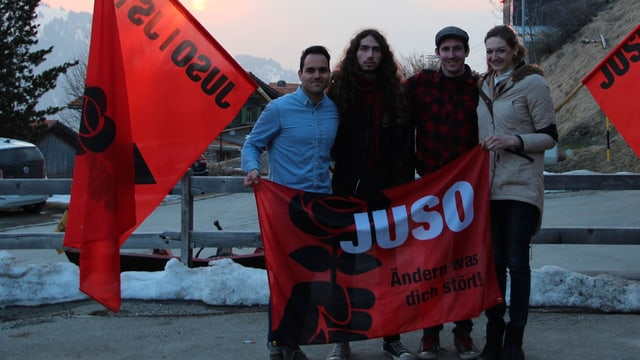 Pascal Pajic, Fabian Camenisch, Dominik Huber e  Deborah Weber cun bandieras da la Juso