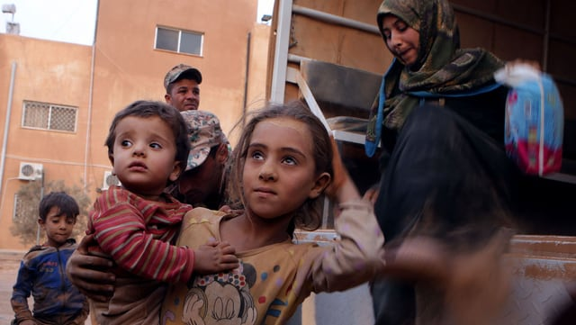 Fugitivs da la Siria che vegnan ord in camiun.