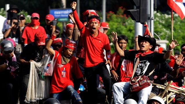 Menschen in roten Kleidern stehen auf einer Barrikade.