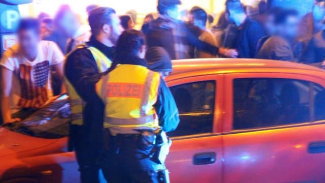 Polizisten führen einen Mann ab.