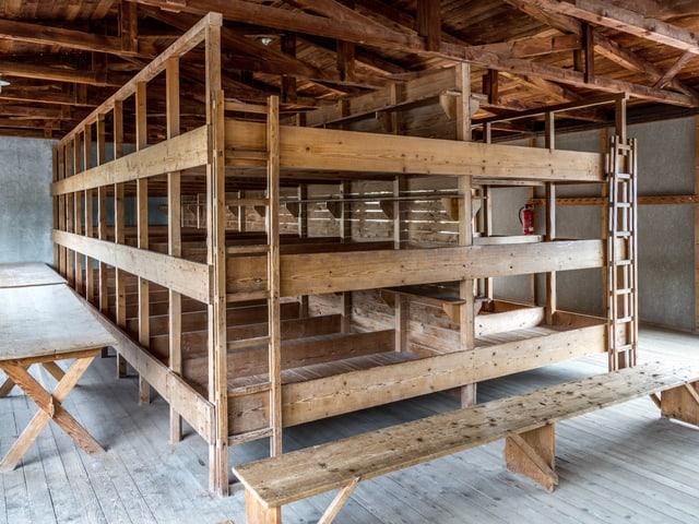 Dreistöckige Hochbetten und Bänke aus Holz.