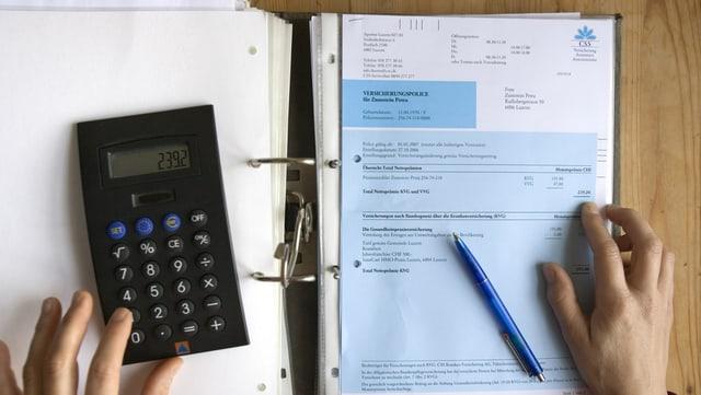 Ordner mit Rechnungen, darüber ein Taschenrechner.