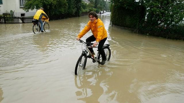 Eine überschwemmte Quartierstrasse, auf der zwei Fahrräder durch die Wassermassen pflügen. Das Wasser steht den Velofahrern dabei fast bis zu den Pedalen.