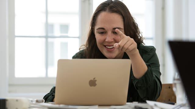 Eine junge Frau sitzt am Laptop.
