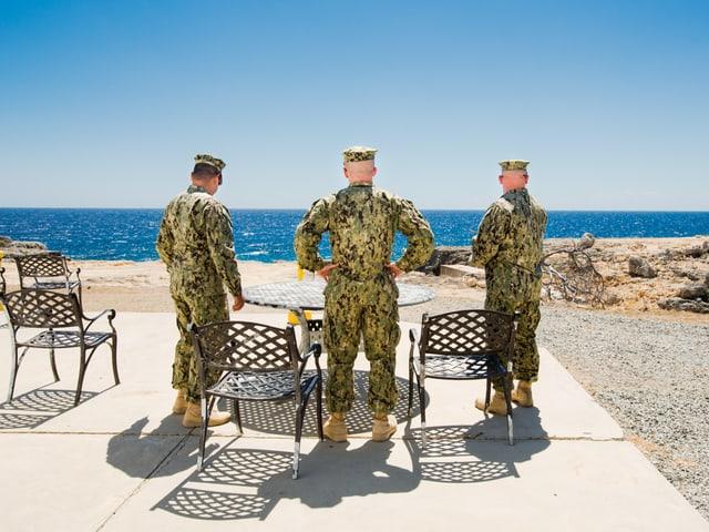 Drei Soldaten von hinten fotografiert. Sie stehen am Strand und schaen aufs Meer.