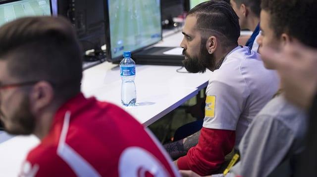 Spieler in Trikots spielen Fifa an den Bildschirmen der Baloise International Gaming Show.