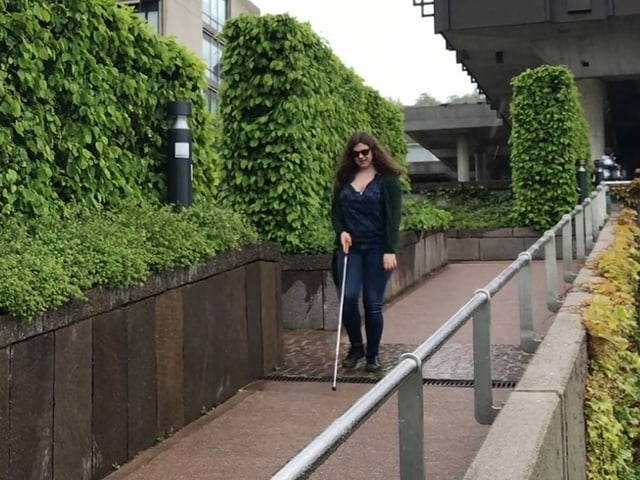 Luana Schena läuft mit ihrem weissen Stock eine Rampe auf dem Campus der Uni runter.