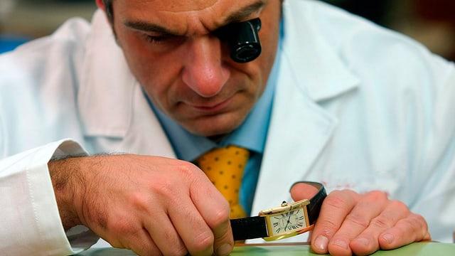 Ein Uhrmacher begutachtet eine Uhr.