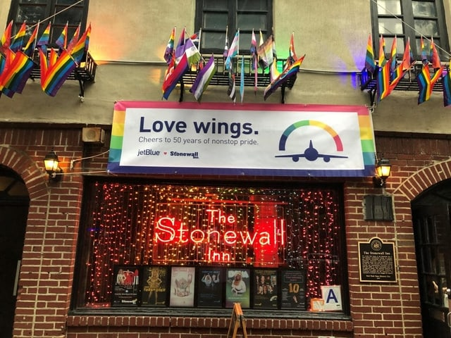 "Ein Bild der Stonewall Bar von aussen - über dem Fenster hängt ein Transparent auf dem steht ""Love wings. Cheers to 50 years of nonstop pride. JetBlue"""