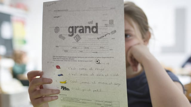 Ein Kind Liest auf einem Arbeitsblatt.