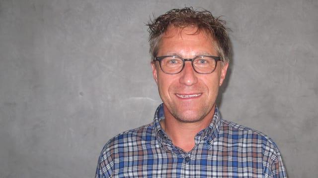 Ein Mann mit Karohemd und Brille.