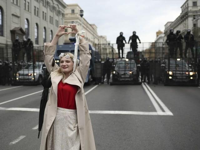 Eine Frau macht mit den Händen ein Herz und steht vor den Sicherheitskräften.