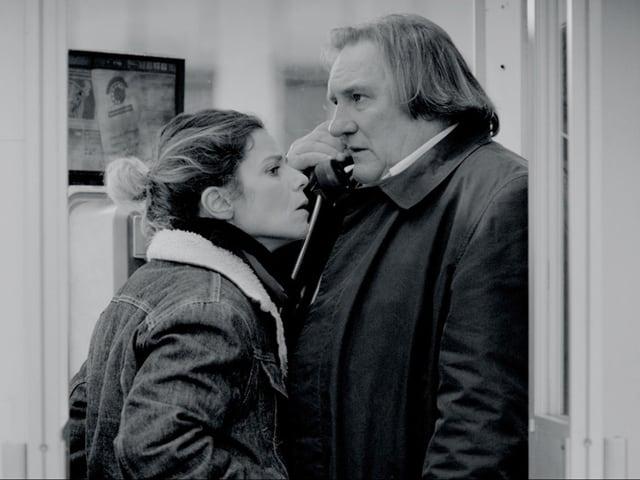 Eine Frau kommt einem Mann nahe, der am telefonieren ist.