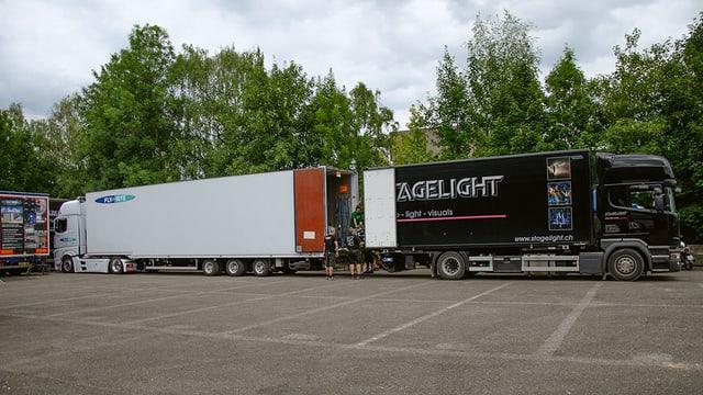 Die zwei Lastwagen in der Totale während dem Umladen