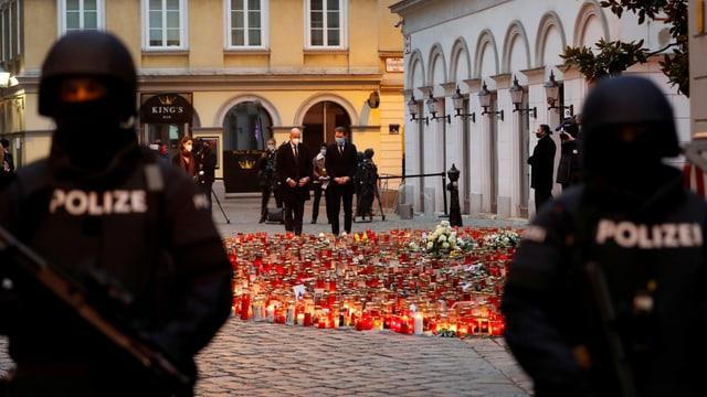 Zwei Polizisten bewachen den Tatort des Wiener Attentats, wo ein Kerzen- und Blumenmeer am Boden steht.
