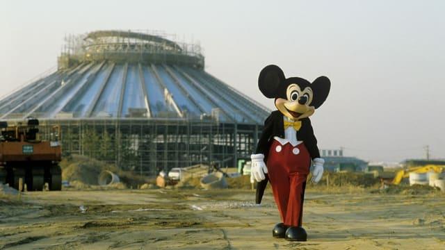 Ein Mickey-Maus-Maskottchen auf einer Baustelle, wo gerade ein neuer Themenpark entsteht.