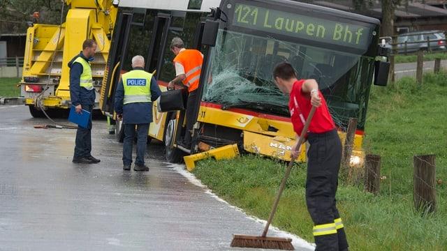 Feuerwehr und Polizei sichern die Unfallstelle eines Postautos mit einem Personenwagen bei Düdingen.
