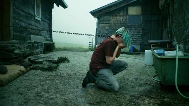 Ein Jugendlicher hockt in einem Hof und hält sich die Hände vor den Mund, als müsste er sich erbrechen.