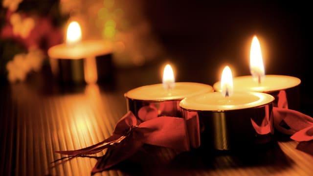 Sanftes Licht von von Rechaudkerzen umrahmt von Weihnachtsdekoration.