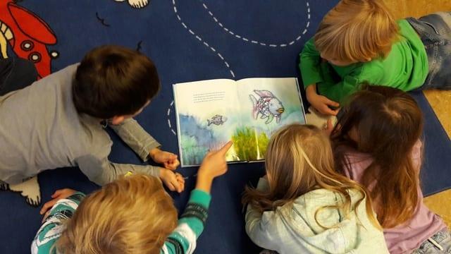 Erstklässler der Schule in Muolen/SG lesen den Regenbogenfisch.