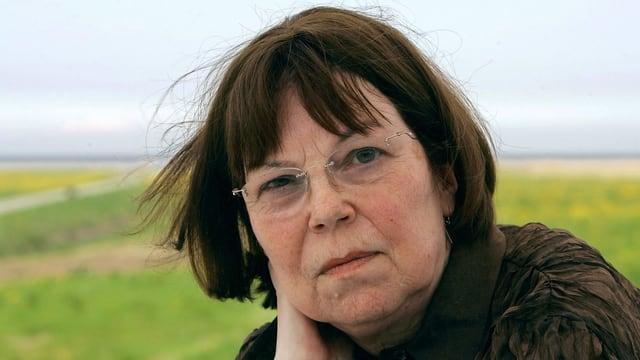 Porträt von Sarah Kirsch mit grüner Landschaft im Hintergrund.