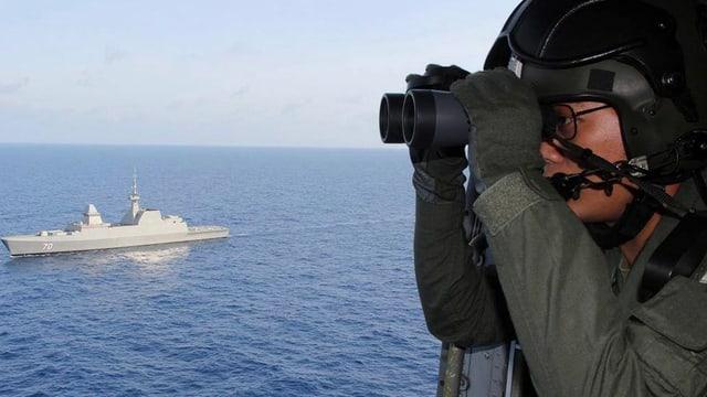 Soldat mit Feldstecher sucht aus der Luft das Meer aub