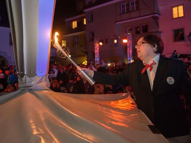 Ein Athlet entzündet mit einer Fackel das olympische Feuer.