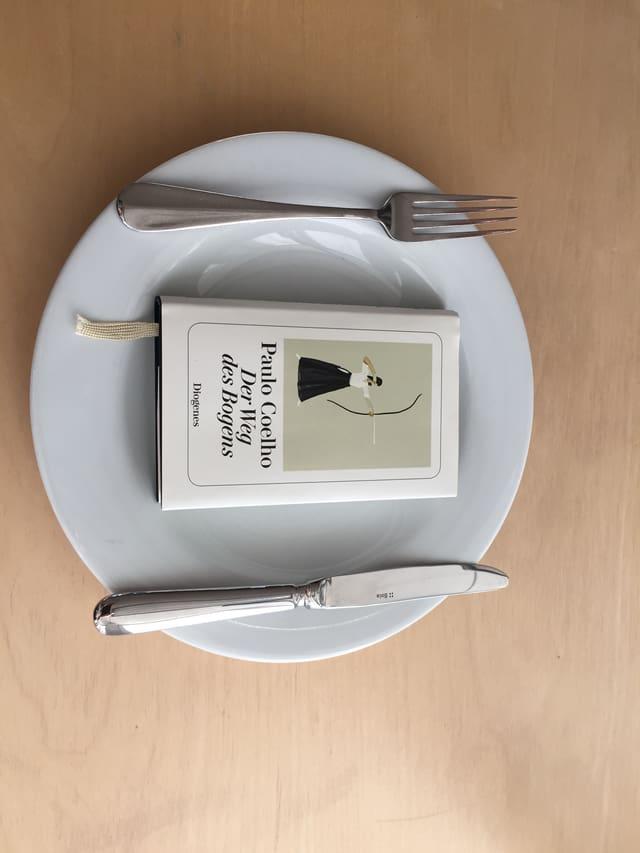 Das Buch «Der Weg des Bogens» von Paulo Coelho liegt auf einem weissen Teller. Messer und Gabel liegen auf dem Teller daneben.