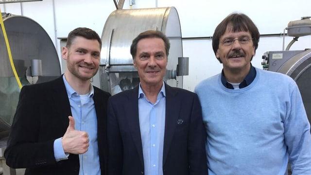 Drei Männer lächeln in die Kamera.