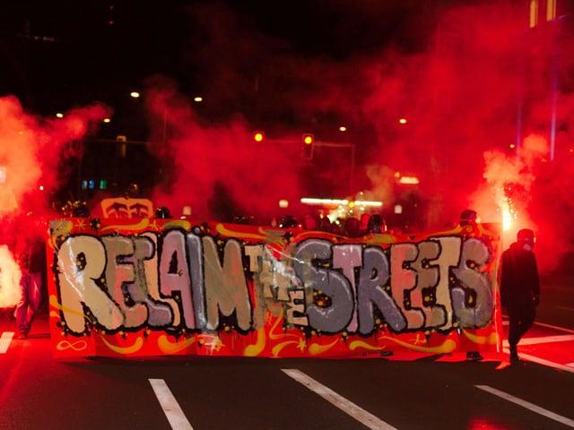 Vermummte Demonstranten der «Reclaim-the-Streets»-Bewegung sind in der Innenstadt von Zürich mit Spruchbändern und Leuchtfackeln unterwegs. (keystone)
